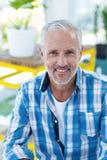 Happy mature man in restaurant. Portrait of happy mature man sitting in restaurant royalty free stock images