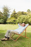 Happy mature man resting in sun lounger Royalty Free Stock Image