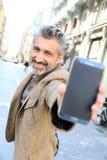 Happy mature man showing smartphone Stock Photo