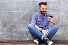 Happy mature man sitting outdoors and using mobile phone Stock Photos