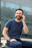 Happy mature man sitting outdoors using mobile phone Royalty Free Stock Image