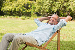Happy mature man sitting on sun lounger Royalty Free Stock Photography