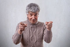 A happy mature man with smile on his face standing against white background pointing his index fingers at camera. Senior mature, e. Lderly man pointing at you Royalty Free Stock Image