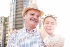 Happy mature man smiling with young woman. Portrait of a happy mature man smiling with young woman. Hispanic father in summer hat and daughter walking outdoor stock photography