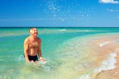 Happy mature man splashing water on the beach Stock Images