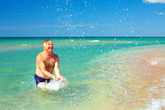 Happy mature man splashing the water on beach Royalty Free Stock Images