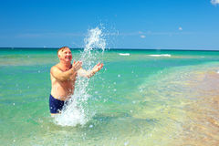 Happy mature man splashing the water on beach Royalty Free Stock Photography