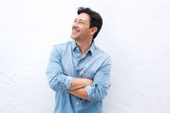 Happy mature man standing with arms crossed against white wall and looking away Royalty Free Stock Images