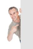 Happy mature man standing behind placard Royalty Free Stock Photos