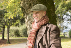 Happy mature man standing under a tree outdoors. royalty free stock image