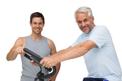 Happy mature man on stationary bike with trainer Stock Photos