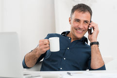 Happy Mature Man Talking On Cellphone. Portrait Of Smiling Mature Man Talking On Cellphone Holding Coffee Cup royalty free stock photos