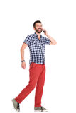 Happy mature man talking on mobile phone. Full length portrait of happy mature man walking and talking on mobile phone over white background royalty free stock photo