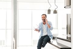 Happy mature man talking on mobile phone. While leaning on a kitchen table at home royalty free stock photography
