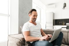 Happy mature man using laptop computer. While sitting on a sofa at home Stock Photos