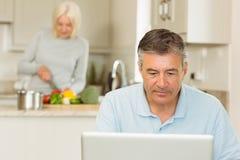Happy mature man using laptop Stock Photos