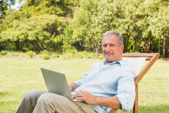 Happy mature man using laptop. In park in deck chair looking at camera Stock Photos