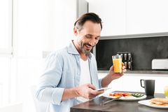 Happy mature man using mobile phone. While having tasty breakfast at the kitchen table royalty free stock photo