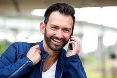 Happy mature man using mobile phone and smiling. Close up portrait of happy mature man using mobile phone and smiling Stock Photo