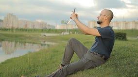 Happy mature man using smartphone near lake stock video