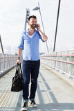 Happy mature man walking on bridge and using mobile phone Royalty Free Stock Photo