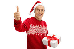 Happy mature man wearing christmas hat holding present and givin. Happy mature man wearing a christmas hat holding a present and giving a thumb up isolated on Stock Images