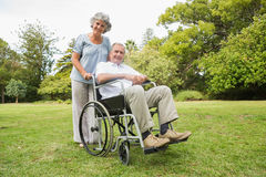 Happy mature man in wheelchair with partner Royalty Free Stock Photo