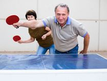 Mature man and woman playing table tennis stock images