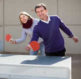 Happy mature man and a woman playing table tennis stock photos