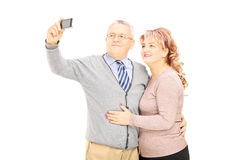 Happy mature man and woman taking pictures of themselves with ph Royalty Free Stock Images