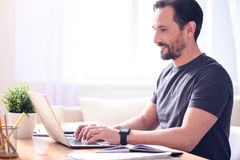 Happy mature man working on his laptop Royalty Free Stock Images