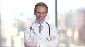 Happy mature middle aged smiling doctor with folded arms, front view. stock video footage