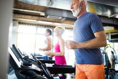 Happy senior people running together on treadmills in gym. royalty free stock photography
