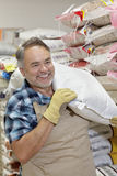 Happy mature salesperson carrying sack in feed store Royalty Free Stock Photos
