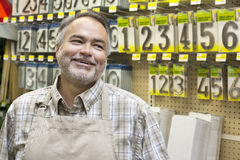 Happy mature salesperson in hardware store looking away Stock Image