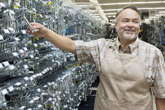 Happy mature salesperson holding metallic equipment while looking away in hardware store Royalty Free Stock Images
