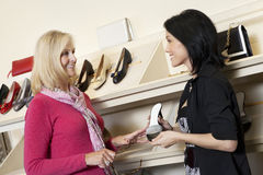 Happy mature salesperson with mid adult customer in shoe store stock photo