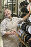 Happy mature salesperson standing by electrical wire spool while looking away in hardware store Stock Photo