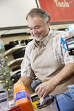 Happy mature salesperson using barcode reader at checkout counter in hardware counter Stock Image