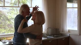 Happy mature senior couple dancing laughing in the kitchen