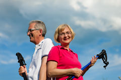 Happy mature or senior couple doing Nordic walking Royalty Free Stock Image