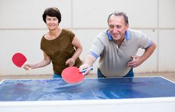 Happy mature spousesn playing table tennis. Man and women playing table tennis royalty free stock image