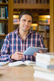 Happy mature student holding tablet PC in the library. Portrait of a happy mature male student holding tablet PC in the library Royalty Free Stock Photography