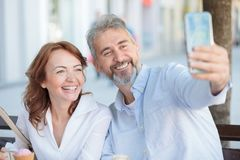 Happy mature tourists couple sitting on a bench and taking a selfie royalty free stock images