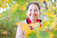 Happy mature woman  in autumn park Stock Photos