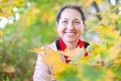 Happy mature woman in autumn park stock photos