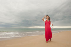 Happy mature woman at beach and with drak clouds Royalty Free Stock Photo