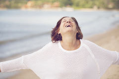Happy mature woman on the beach stock photography