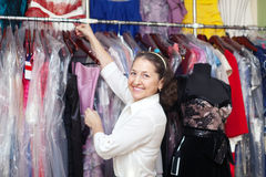 Happy mature woman  chooses  gown Stock Image