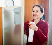 Happy mature woman cleaning  glass Stock Photo
